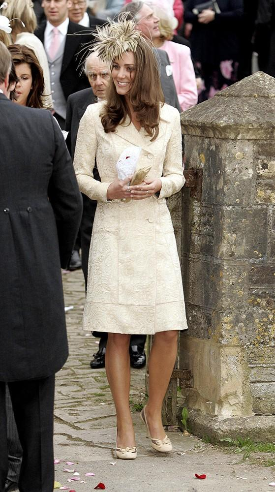 Kate looked lovely in a long cream coat and fancy fascinator at a friend's wedding.