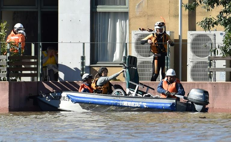 Rescuers moved people by boat from a retirement home that was flooded after Typhoon Hagibis hit Japan (AFP Photo/Kazuhiro NOGI)