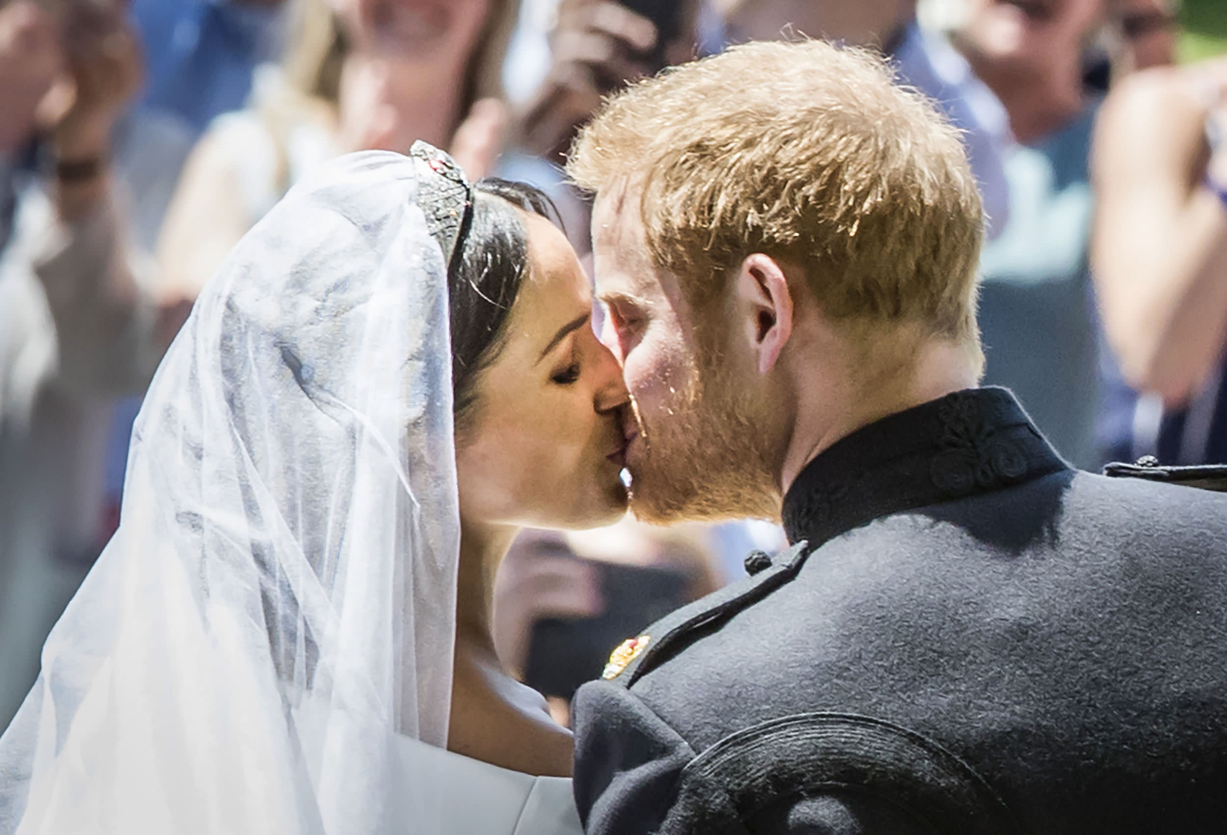 TOPSHOT - Britain's Prince Harry, Duke of Sussex kisses his wife Meghan, Duchess of Sussex as they leave from the West Door of St George's Chapel, Windsor Castle, in Windsor, on May 19, 2018 after their wedding ceremony. (Photo by Danny Lawson / POOL / AFP)        (Photo credit should read DANNY LAWSON/AFP/Getty Images)