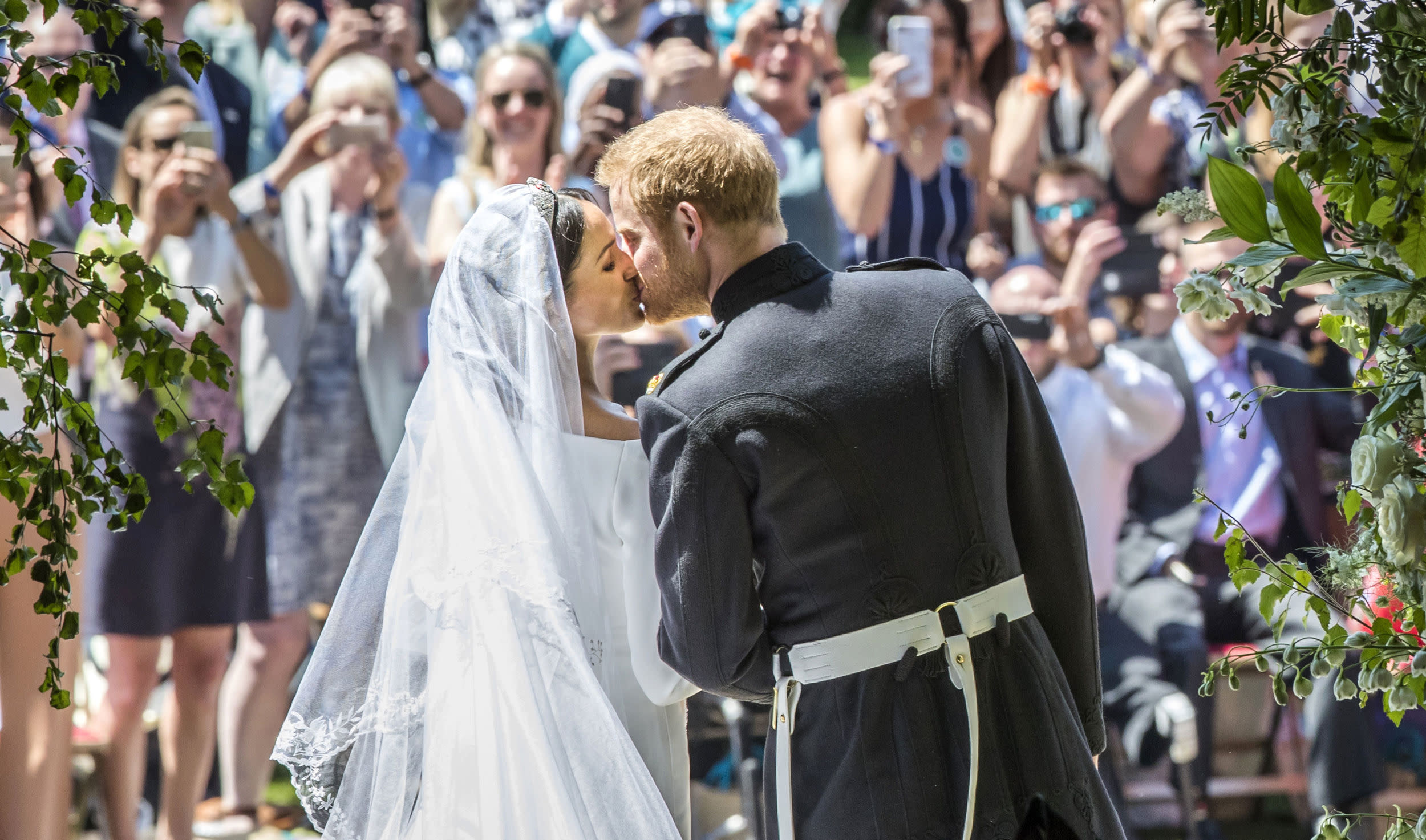 <p>Britain's Prince Harry, Duke of Sussex kisses his wife Meghan, Duchess of Sussex as they leave from the West Door of St George's Chapel, Windsor Castle, in Windsor, on May 19, 2018 after their wedding ceremony.</p>  <p>(Photo by Danny Lawson / POOL / AFP)</p>