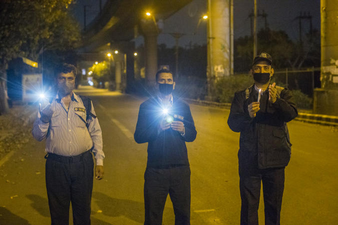 NEW DELHI, INDIA - APRIL 05: Indians hold candles and smartphone flashlights on a deserted main road for nine minutes to show solidarity in the fight against the coronavirus as a nationwide lockdown continues on April 05, 2020 in New Delhi, India. India is under a 21-day lockdown to fight the spread of the virus. After an appeal by Indian Prime Minister Narendra Modi, millions of Indians on Sunday switched off lights in their houses at 9 pm for nine minutes to show solidarity in the country's fight against the coronavirus. The lockdown has already disproportionately hurt marginalized communities due to the loss of livelihood and lack of food, shelter and other basic needs. The lockdown has left tens of thousands of out-of-work migrant workers stranded, with rail and bus services shut down. The closing of state borders has caused disruption in the supply of essential goods, leading to inflation and fear of shortages. There are more than 3,500 positive coronavirus cases in India with currently 99 deaths. (Photo by Yawar Nazir/Getty Images)