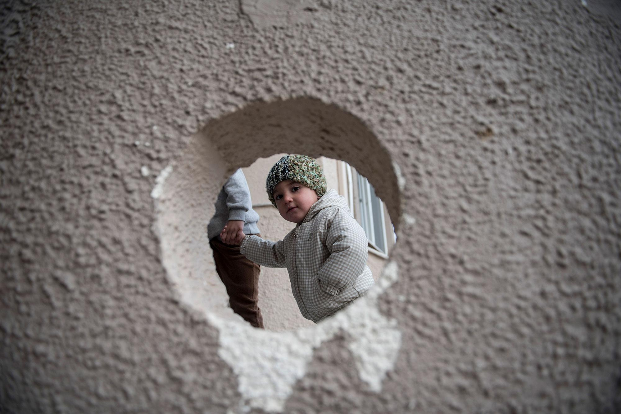 <p>A Yazidi refugee child is seen through a hole on a wall, in the northern Greek village of Agios Athanasios, near Thessaloniki city, on Wednesday, Dec. 21, 2016. Over 62,000 refugees and other migrants stuck in Greece after a series of Balkan border closures and a European Union deal with Turkey to stop migrant flows.(Photo: Giannis Papanikos/AP) </p>