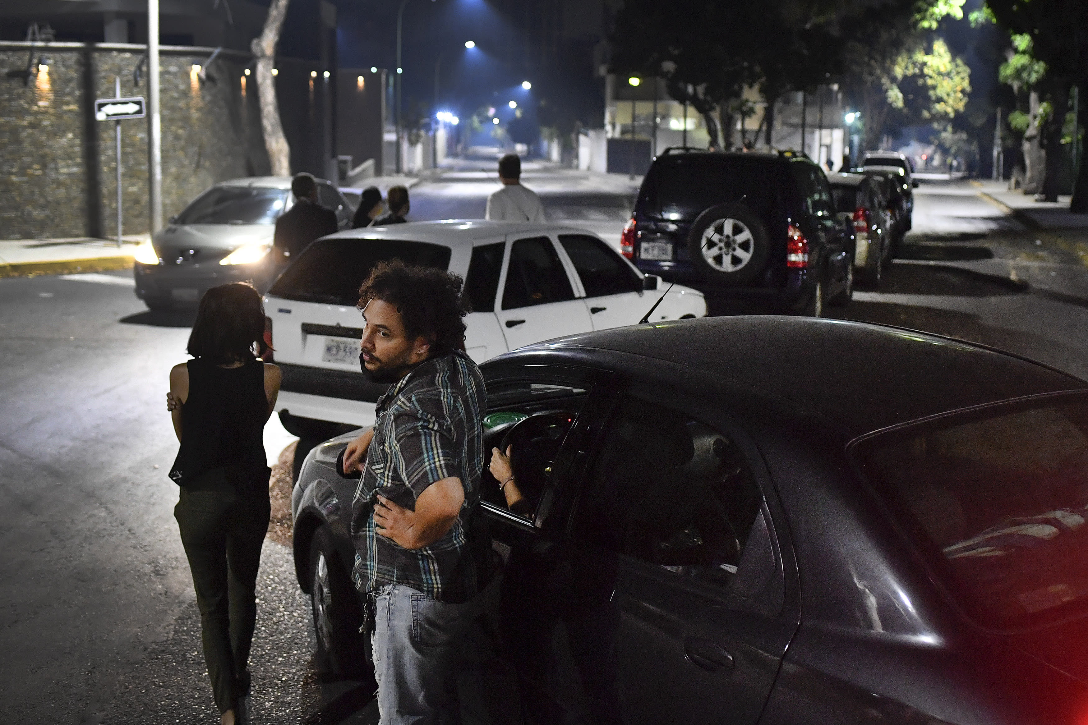 People stand close to their vehicles as they wait in line to fill up their vehicles with gasoline in Caracas, Venezuela, Saturday, April 11, 2020. Lines at gas stations around the country's capital looked getting longer Saturday. (AP Photo/Matias Delacroix)