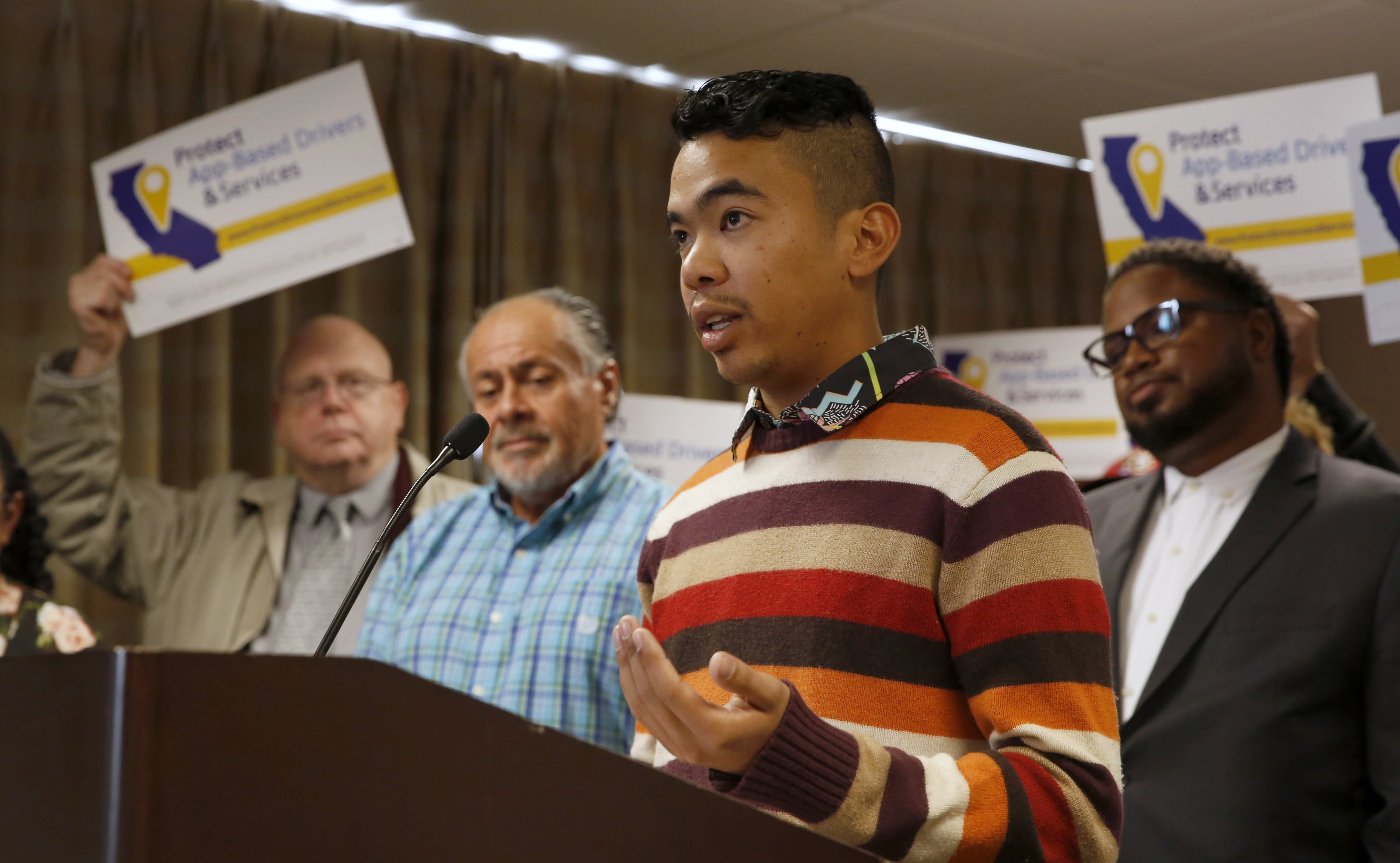 Akamine Kiarie, a college student, says working for Lyft as an independent contractor gives him the freedom to work when he wants and still be able to attend classes, during a news conference in Sacramento, Calif., Tuesday, Oct. 29, 2019. Kiarie supports a proposed ballot initiative by a group called Protect App-Based Drivers and Services that it will push a ballot initiative challenging a recently signed law that makes it harder for companies to label workers as independent contractors. If approved by voters the initiative would guarantee that drivers remain independent contractors but also receive a minimum wage and money for health insurance. (AP Photo/Rich Pedroncelli)