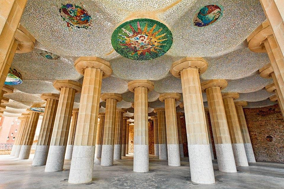 His investigation into classical architecture extended to Barcelona's Parc Güell, where Doric-inspired columns fill the market hall. But in signature Gaudí style, the ceiling is decorated with colorful mosaics. The park was built between 1900 and 1914.