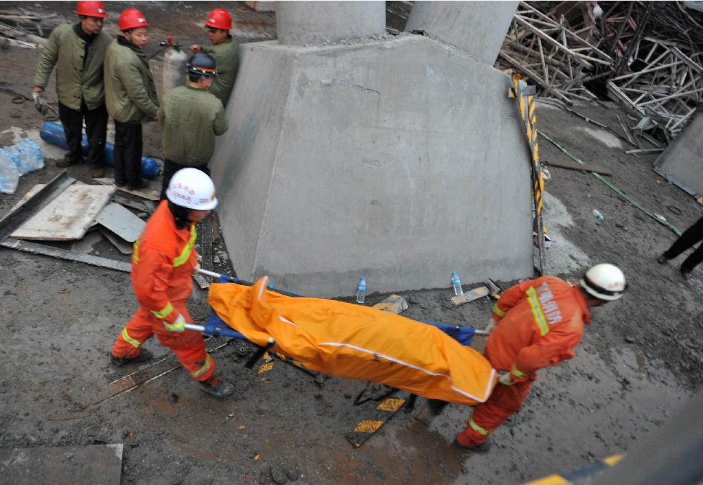 Workers carry a body on a stretcher from the remains of a collapsed platform in a cooling tower at a power station at Fengcheng in China's Jiangxi province on November 24, 2016 (AFP Photo/)