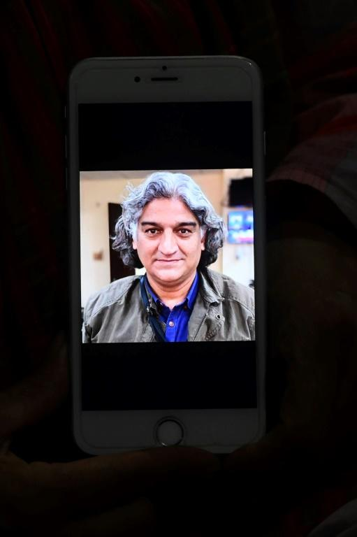 Kaneez Sughra, wife of Pakistani journalist Matiullah Jan, displays a photograph of her husband on her mobile phone; Jan was freed late in the day (AFP Photo/Aamir QURESHI)