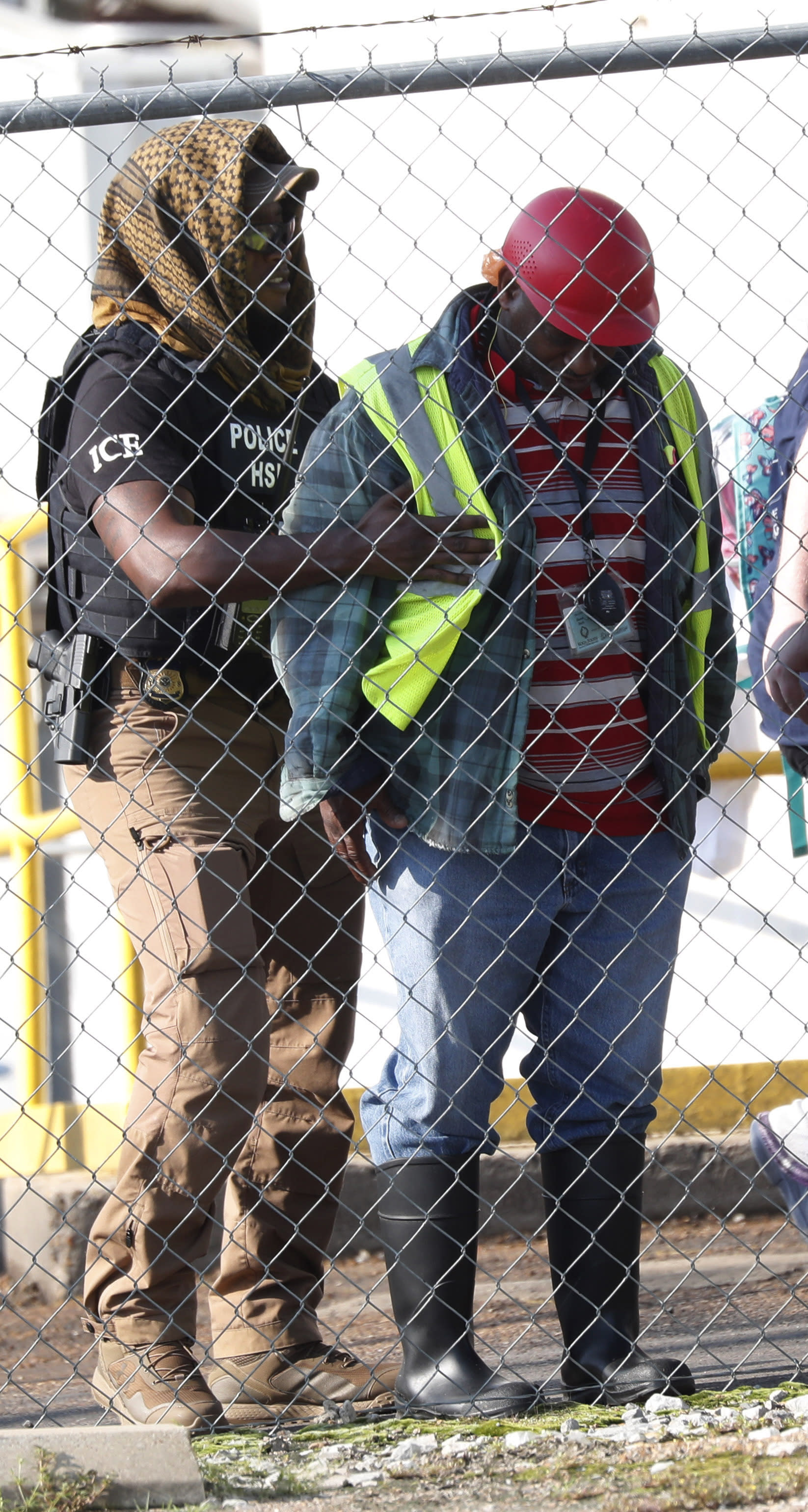 A federal agent searches a man as U.S. immigration officials raid the Koch Foods Inc., plant in Morton, Miss., Wednesday, Aug. 7, 2019. U.S. immigration officials raided several Mississippi food processing plants on Wednesday and signaled that the early-morning strikes were part of a large-scale operation targeting owners as well as employees. (AP Photo/Rogelio V. Solis)