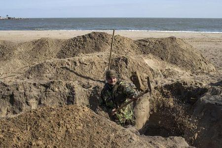 A Ukrainian serviceman digs trenches on a beach in the port city of Mariupol on the Azov Sea, March 20, 2015. REUTERS/Marko Djurica