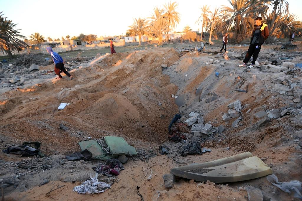 Libyans stand next to a crater and debris at the site of a jihadist training camp, targeted in a US air strike, near the Libyan city of Sabratha on February 19, 2016