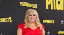 Rebel Wilson looks red hot in fit-and-flare satin dress