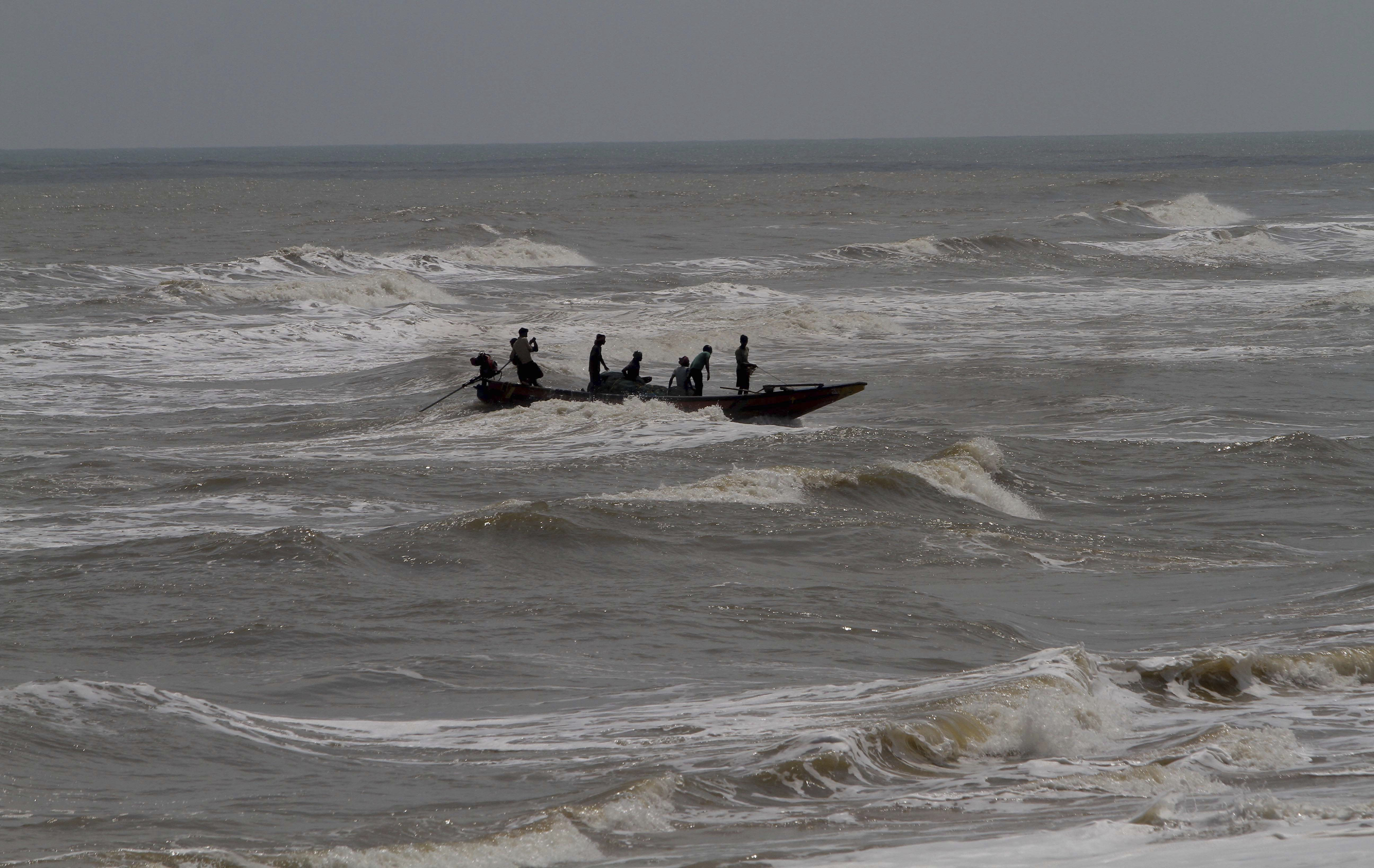 In this Wednesday, May 1, 2019 photo, Indian fishermen attempt to bring their boat ashore amid strong winds at Chandrabhaga beach in Puri district of eastern Odisha state, India. Hundreds of thousands of people were evacuated along India's eastern coast on Thursday as authorities braced for a cyclone moving through the Bay of Bengal that was forecast to bring extremely severe wind and rain. (AP Photo)