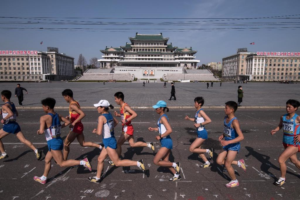 Competitors run through Kim Il-Sung square during the Pyongyang Marathon in the North Korean capital (AFP Photo/Ed JONES)