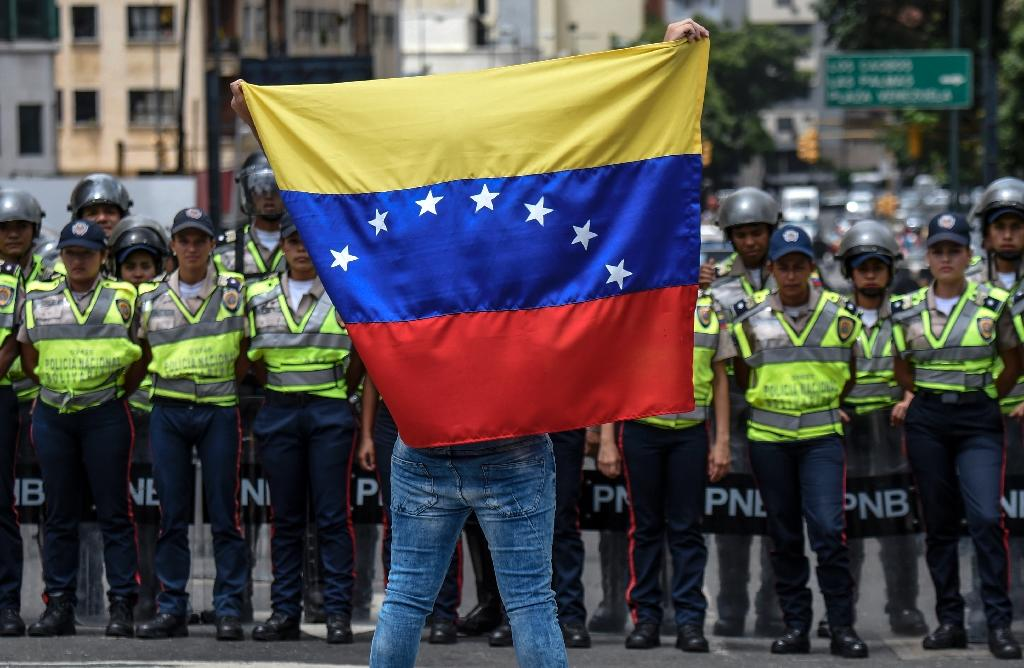 A member of Venezuela's opposition waves a national flag in front of police during a demonstration in Caracas (AFP Photo/Juan Barreto)