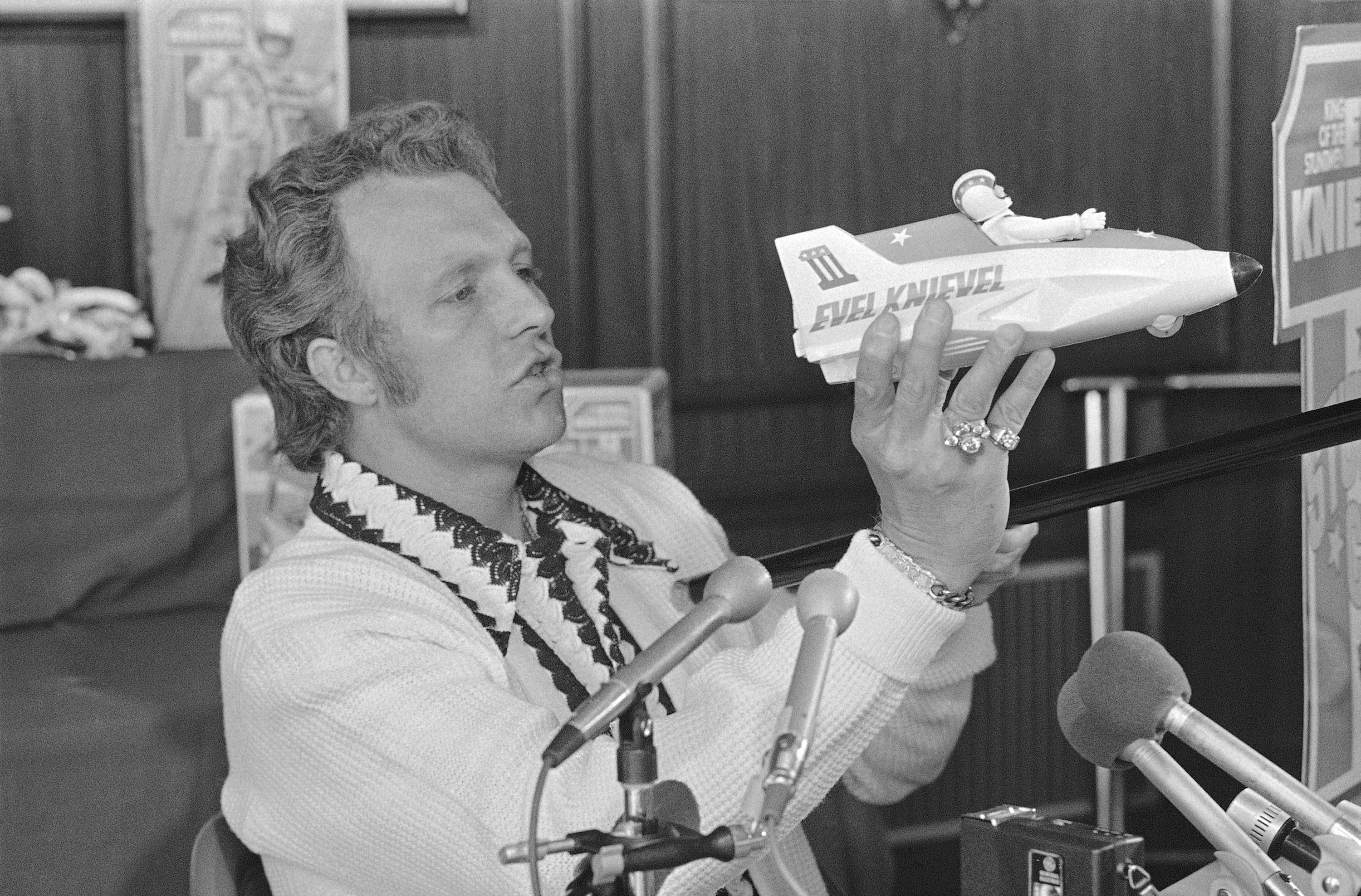 """FILE - In this Sept. 3, 1974, file photo, Evel Knievel talks about his upcoming Snake River canyon, Idaho, jump during a news conference in New York. Evel Knievel's son is on a collision course with the Walt Disney Co. and Pixar over a movie daredevil character named Duke Caboom. A federal trademark infringement lawsuit filed Tuesday, Sept. 22, 2020, in Las Vegas accuses the moviemaker of improperly basing the """"Toy Story 4"""" character on Knievel. (AP Photo, File)"""