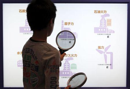 A boy uses a magnifying glass to look at a screen showing the amount of carbon dioxide emissions to generate electricity in various ways, at a nuclear museum beside the Chubu Electric Power's Hamaoka Nuclear Power Station in Omaezaki, Shizuoka Prefecture, in this May 5, 2011 file photo. REUTERS/Issei Kato/Files
