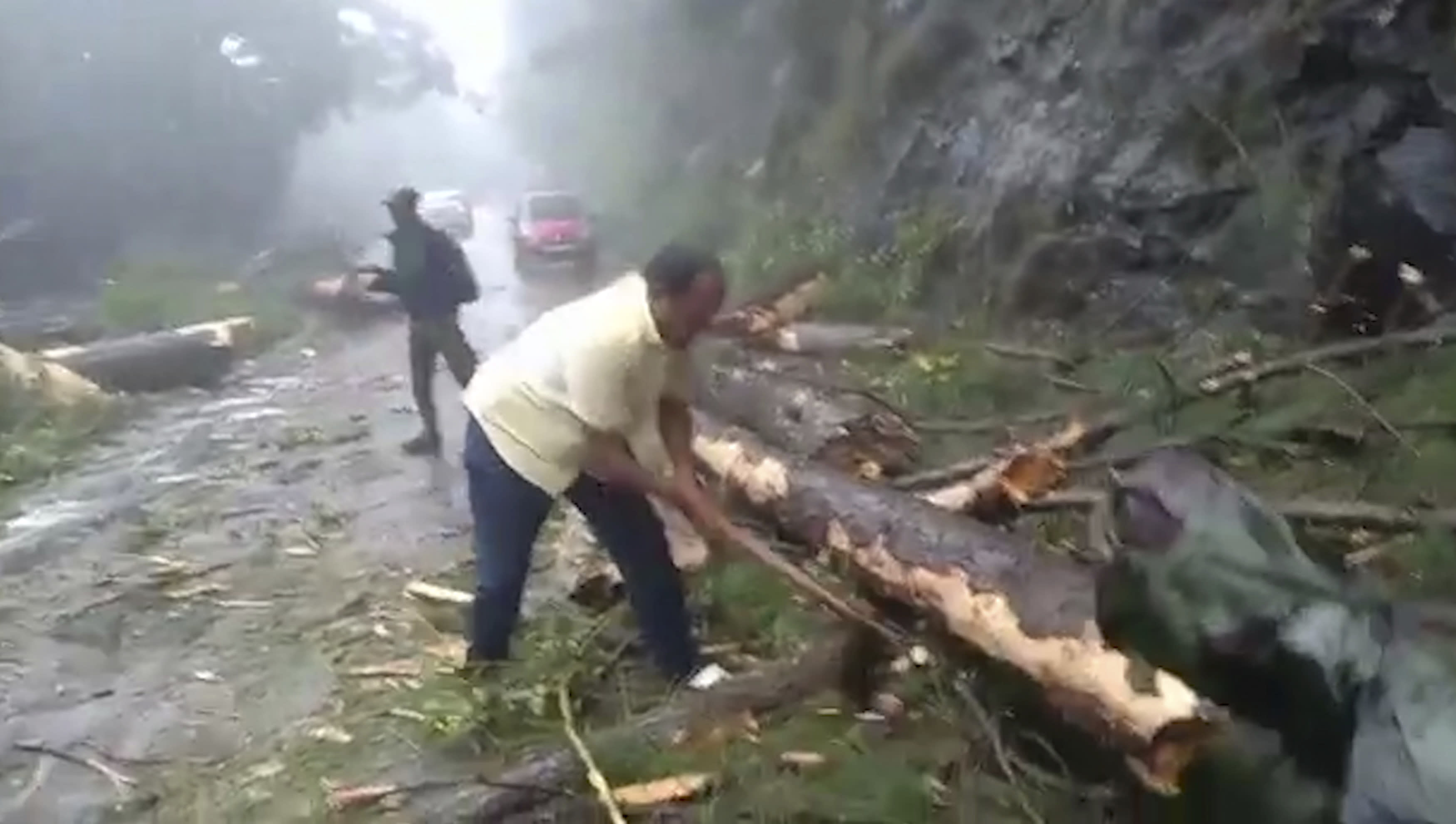 In this grab made from video provided by KK Productions, a man chops branches from a tree to clear a road after a cyclone struck Cuddalore, in the southern Indian state of Tamil Nadu, Friday, Nov. 16, 2018. A cyclone hit the coast of southern India on Friday, killing more than 10 people and damaging homes after more than 80,000 residents were evacuated. (KK Production via AP)
