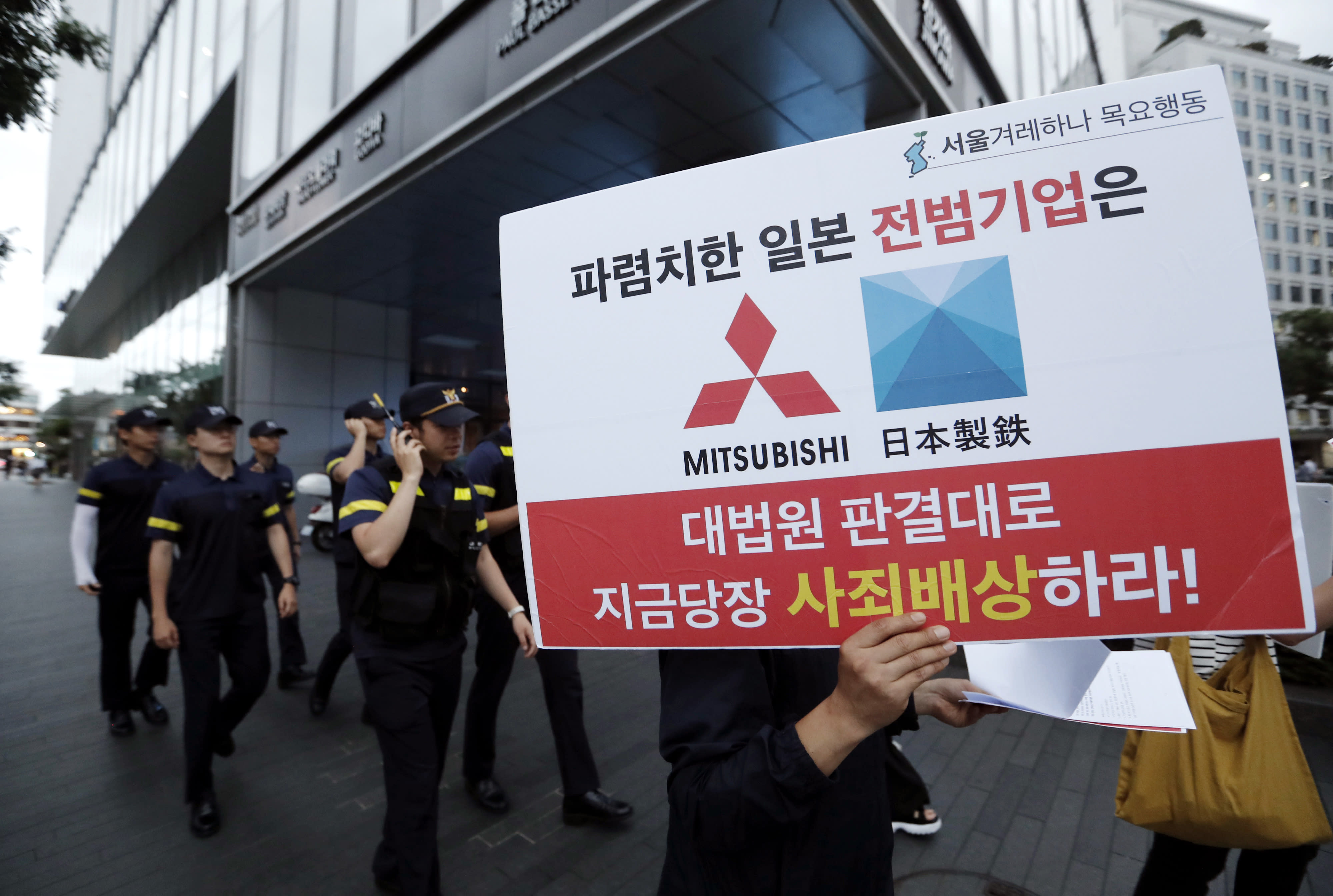 "FILE - In this July 11, 2019, file photo, a protester with a banner walks to attend a rally denouncing the Japanese government's decision on their exports to South Korea in front of the Japanese Embassy in Seoul, South Korea. The modern legacy of a dark chapter in Japan's history, when hundreds of thousands of people were brought from the Korean Peninsula and other Asian nations to work in logging, in mines, on farms and in factories as forced labor, lives on in the companies that came to dominate the Japanese economy after World War II. Many of those companies are still facing demands for compensation that they say were settled by treaty decades ago. The sign reads ""The shameless Japanese company should immediately compensate for its war crimes in accordance with the Supreme Court ruling."" (AP Photo/Ahn Young-joon, File)"