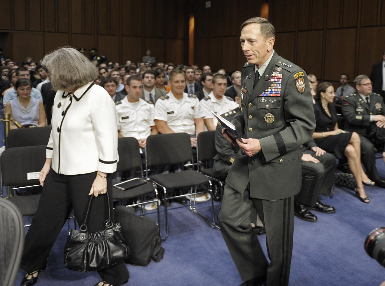 FILE - In this June 23, 2011, file photo, Gen. David Petraeus, center, walks with his wife Holly, left, past a seated Paula Broadwell, rear right, as he arrives to appear before the Senate Intelligence Committee during a hearing on his nomination to be Director of the Central Intelligence Agency on Capitol Hill in Washington. Petraeus quit Nov. 9, 2012, after acknowledging an extramarital relationship. As questions arise about the extramarital affair between Petraeus and his biographer, Paula Broadwell, she has remained quiet about details of their relationship. However, information has emerged about Jill Kelley, the woman who received the emails from Broadwell that led to the FBI's discovery of Petraeus' indiscretion. (AP Photo/Cliff Owen, File)