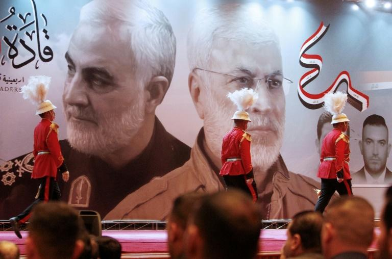 Members of the Iraqi honour guard walk past huge portraits of Iran's late top general Qasem Soleimani (L) and Iraqi paramilitary commander Abu Mahdi al-Muhandis, both killed in a US drone strike last month, during a memorial service (AFP Photo/SABAH ARAR)