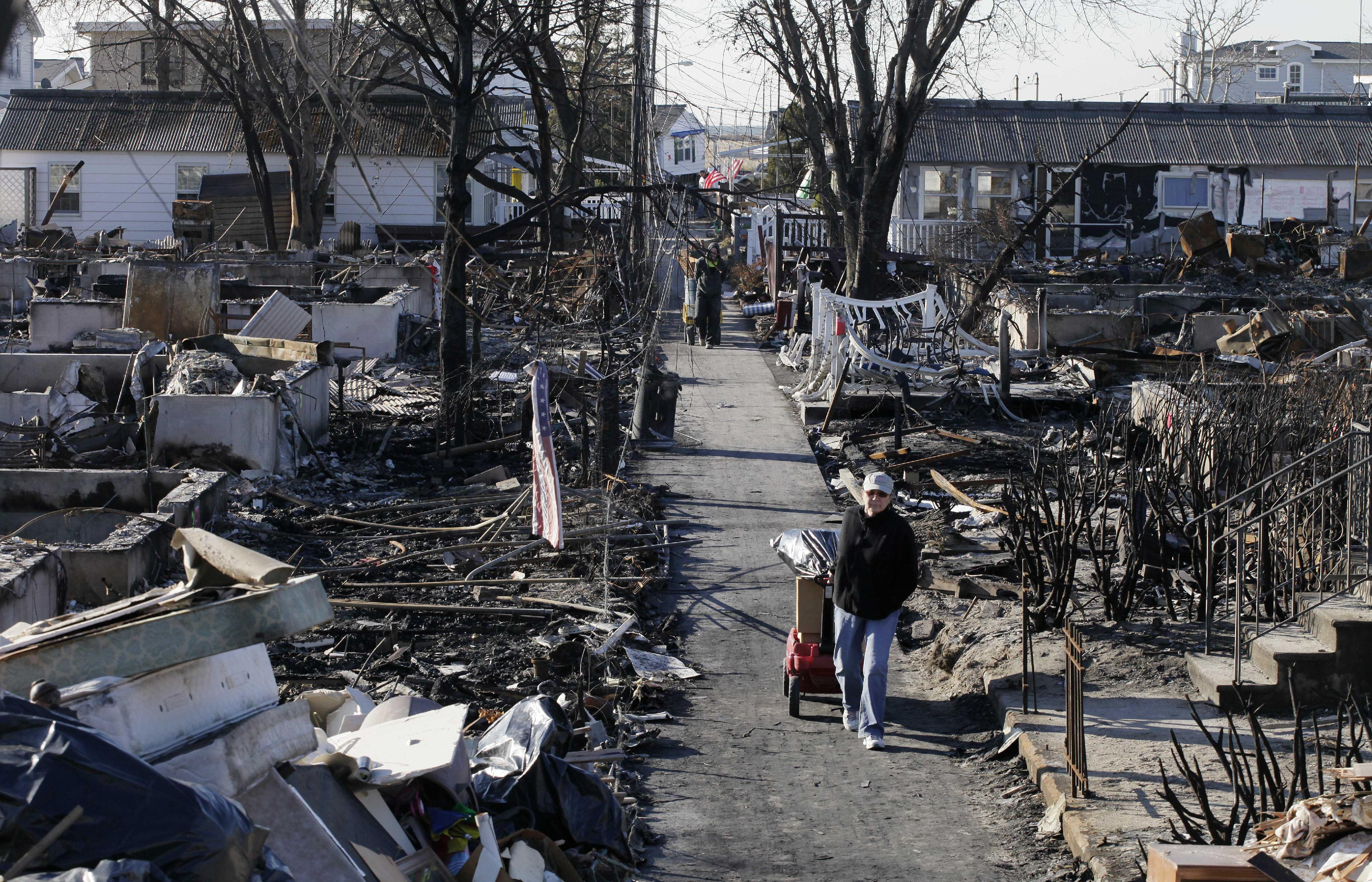 Louise McCarthy carts belongings from her flood-damaged home as she passes the charred ruins of other homes in the Breezy Point section of the Queens borough of New York, Wednesday, Nov. 14, 2012. A fire destroyed more than 100 homes in the oceanfront community during Superstorm Sandy. (AP Photo/Mark Lennihan)