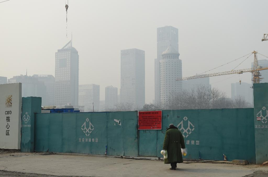 "A man walks towards a ""red alert"" pollution notice announcing the suspension of outdoor work, on an entrance to a closed construction site on a polluted day in Beijing on December 20, 2015 (AFP Photo/Greg Baker)"