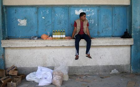 A Palestinian man sits next to food supplies at an aid distribution center run by United Nations Relief and Works Agency (UNRWA) in Khan Younis in the southern Gaza Strip September 1, 2018. REUTERS/Ibraheem Abu Mustafa