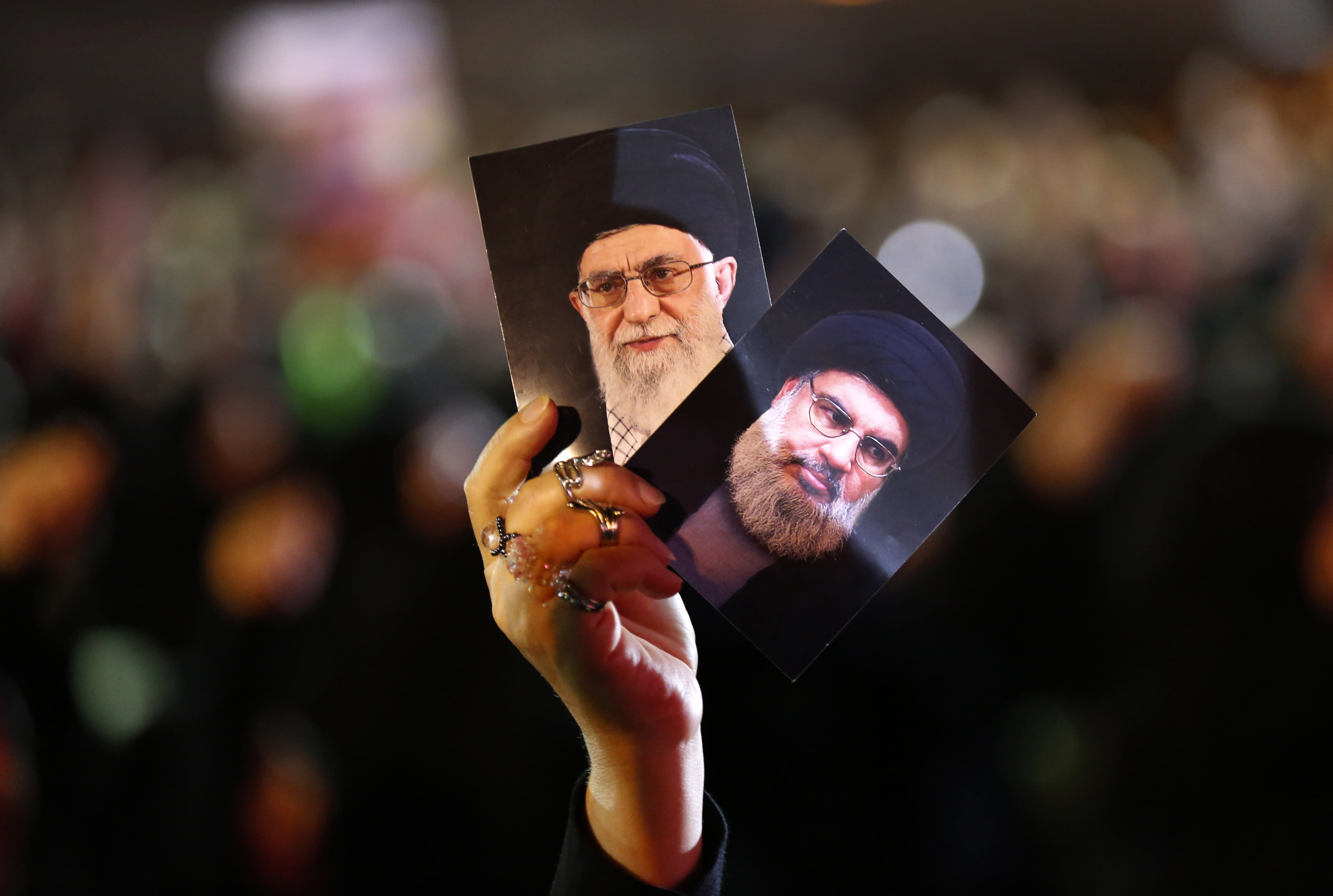 A Hezbollah supporter holds up portraits of Hezbollah leader Sheikh Hassan Nasrallah, right, and Iran's supreme leader Ayatollah Ali Khamenei, left, during activities to mark the ninth of Ashura, a 10-day ritual commemorating the death of Imam Hussein, in a southern suburb of Beirut, Lebanon, Wednesday, Sept. 19, 2018. Hassan Nasrallah says his group may reduce the number of its fighters in Syria because of an easing of the conflict, particularly after a recent Russian-Turkey agreement that prevented an offensive on the last rebel stronghold. (AP Photo/Hussein Malla)