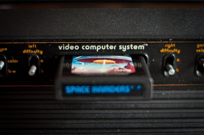 [UNVERIFIED CONTENT] Atari 2600 VCS console, close up of inserted cartridge and central switches. Space Invaders game is inserted. Difficulty switches visible. Narrow depth of field. Dust visible.