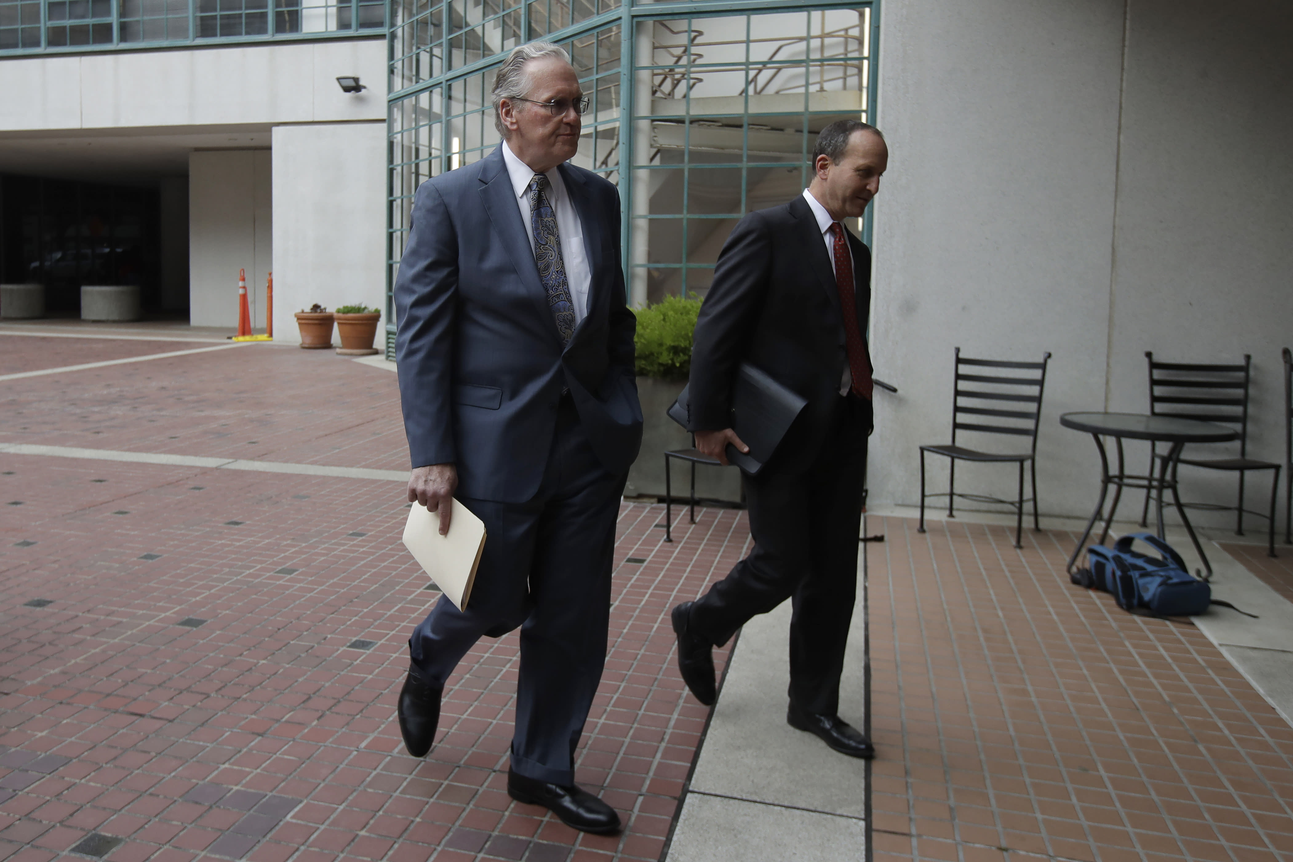 Pacific Gas and Electric Company (PG&E) CEO Bill Johnson, left, walks toward the California Public Utilities Commission headquarters before a meeting in San Francisco, Friday, Oct. 18, 2019. (AP Photo/Jeff Chiu)