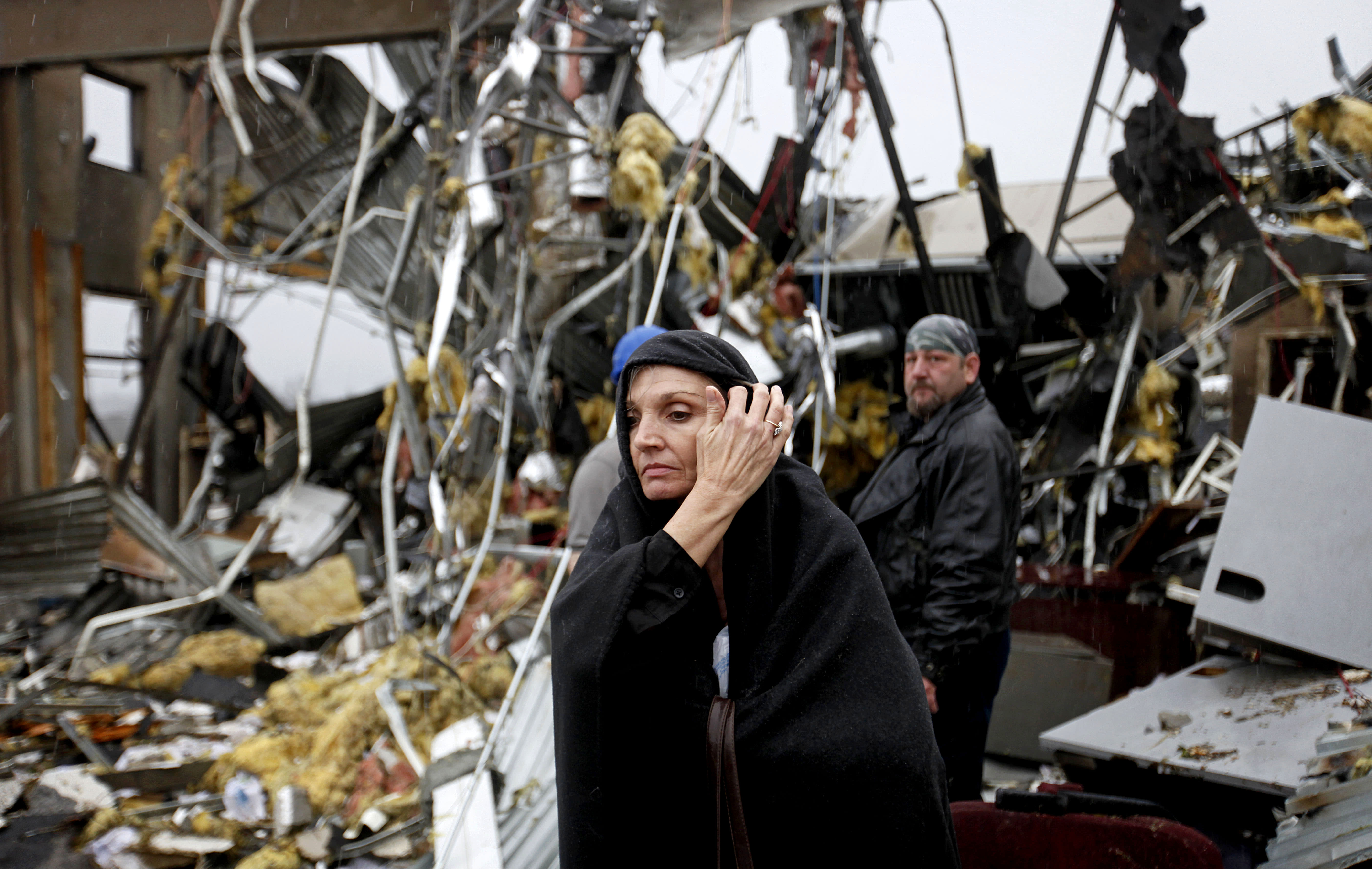 Pam Parker sifts through debris while looking for any personal belongings in the area where she was sitting at her desk when a tornado struck the Daiki plant, a metal fabrication company where she works in accounts payable, Wednesday, Jan. 30, 2013, in Adairsville, Ga. (AP Photo/David Goldman)