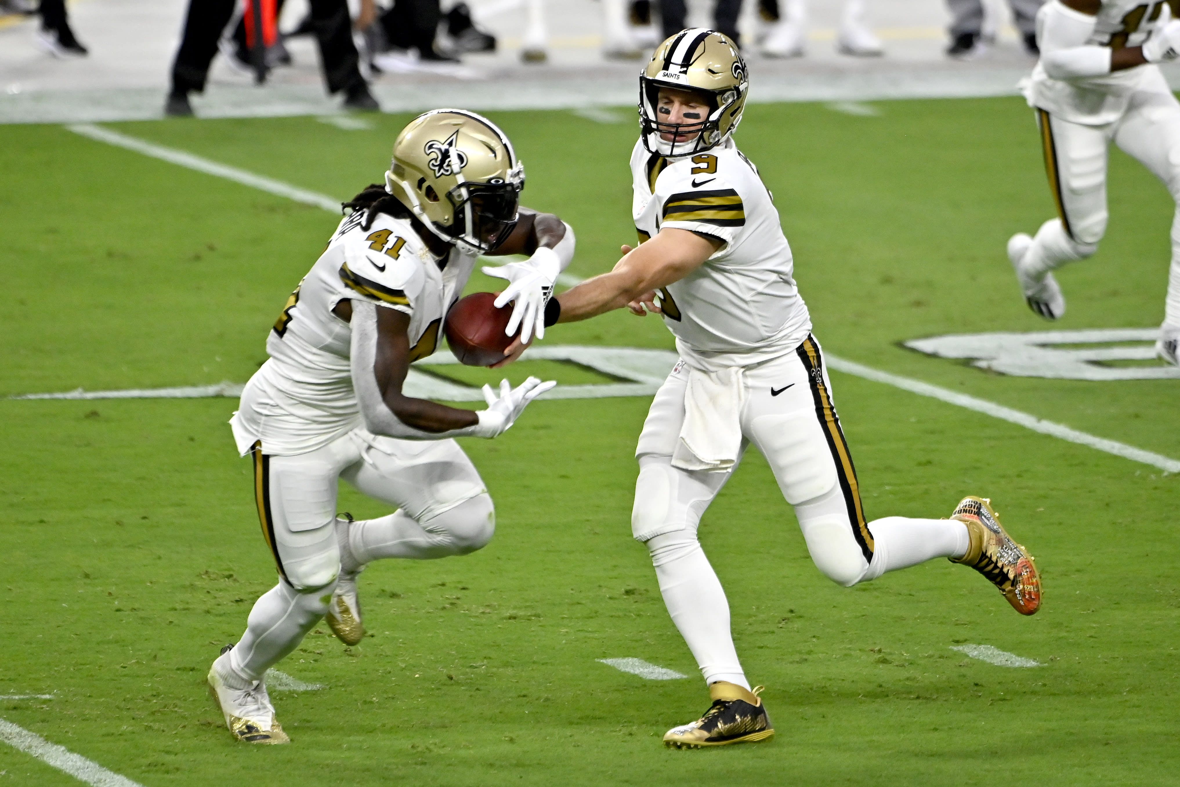 New Orleans Saints quarterback Drew Brees (9) hands the ball off to running back Alvin Kamara (41) during the first half of an NFL football game against the Las Vegas Raiders, Monday, Sept. 21, 2020, in Las Vegas. (AP Photo/David Becker)