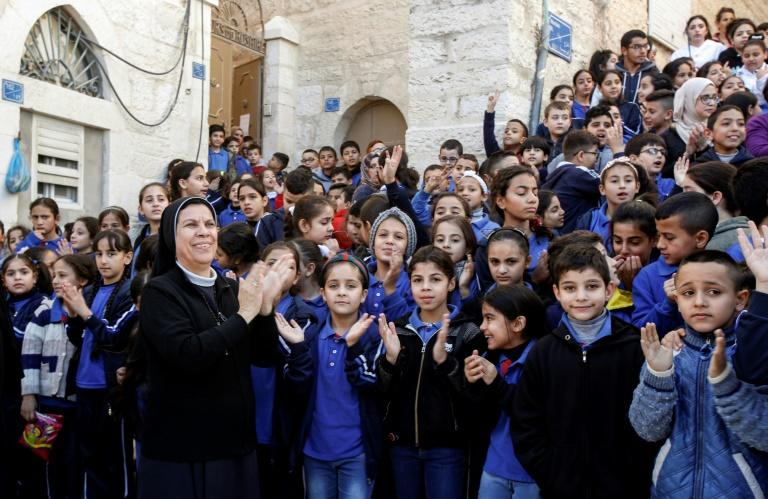 Palestinian schoolchildren mark the relic's arrival at the Church of the Nativity compound in Bethlehem (AFP Photo/Musa Al SHAER)