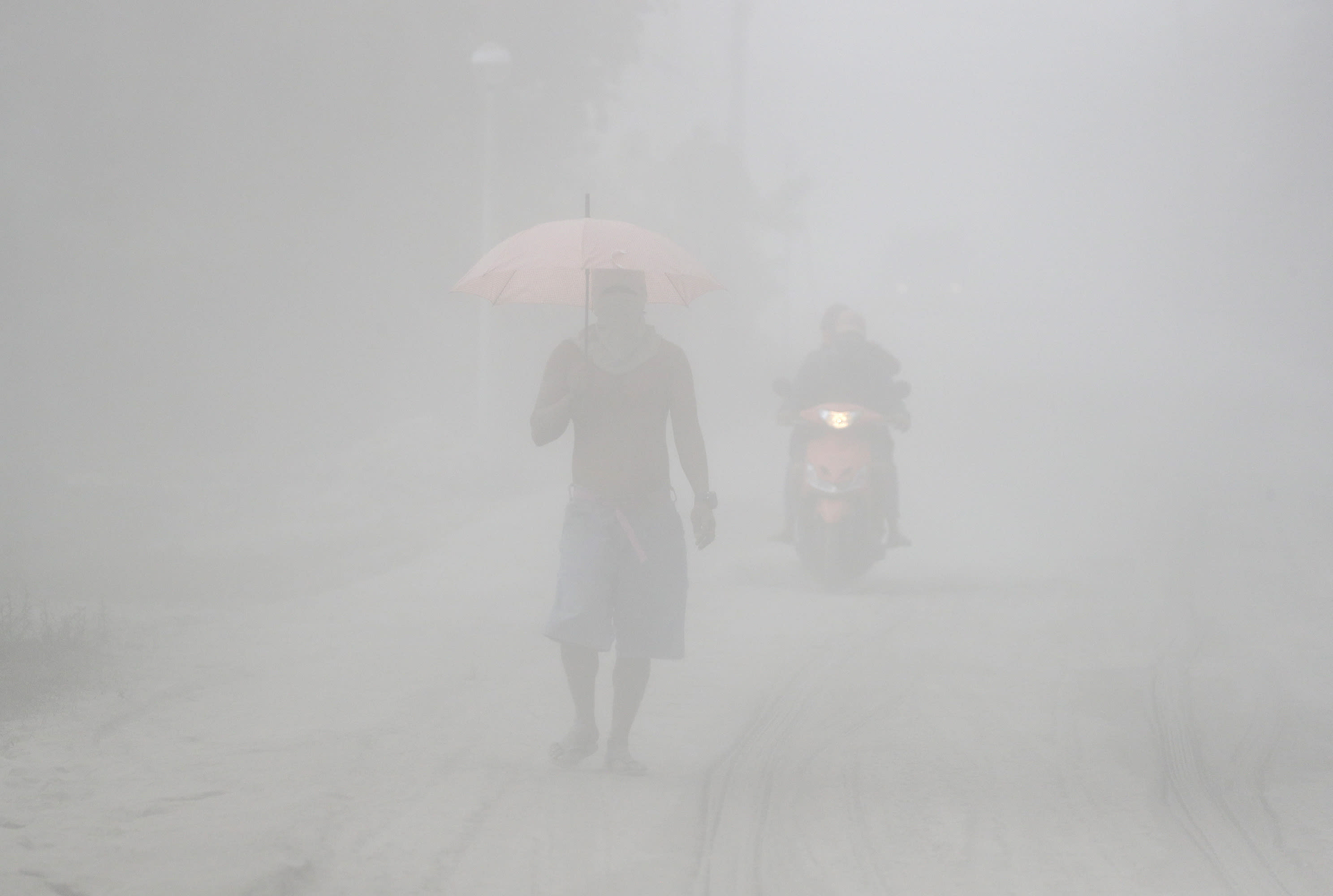 A man walks through a cloud of volcanic ash as he evacuates to safer grounds as Taal volcano in Tagaytay, Cavite province, southern Philippines on Monday, Jan. 13, 2020. Red-hot lava is gushing from the volcano after a sudden eruption of ash and steam that forced residents to flee and shut down Manila's airport, offices and schools. (AP Photo/Aaron Favila)
