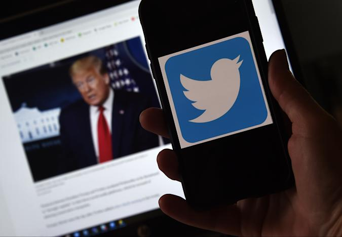 """In this photo illustration, a Twitter logo is displayed on a mobile phone with a President Trump's picture shown in the background on May 27, 2020, in Arlington, Virginia. - US President Donald Trump threatened Wednesday to shutter social media platforms after Twitter for the first time acted against his false tweets, prompting the enraged Republican to double down on unsubstantiated claims and conspiracy theories. Twitter tagged two of Trump's tweets in which he claimed that more mail-in voting would lead to what he called a """"Rigged Election"""" this November. (Photo by Olivier DOULIERY / AFP) (Photo by OLIVIER DOULIERY/AFP via Getty Images)"""