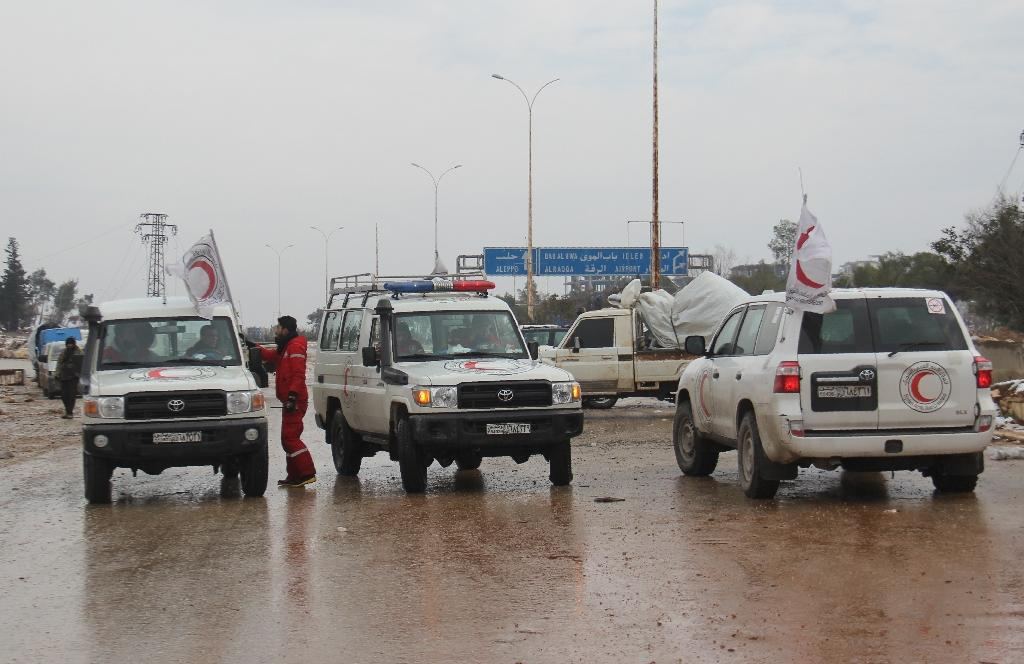 Staff of the Syrian Red Crescent wait on a road in December 2016 for evacuees from Fuaa and Kafraya, two Shiite-majority villages in northwestern Syria that are under siege by the Sunni Muslim rebels