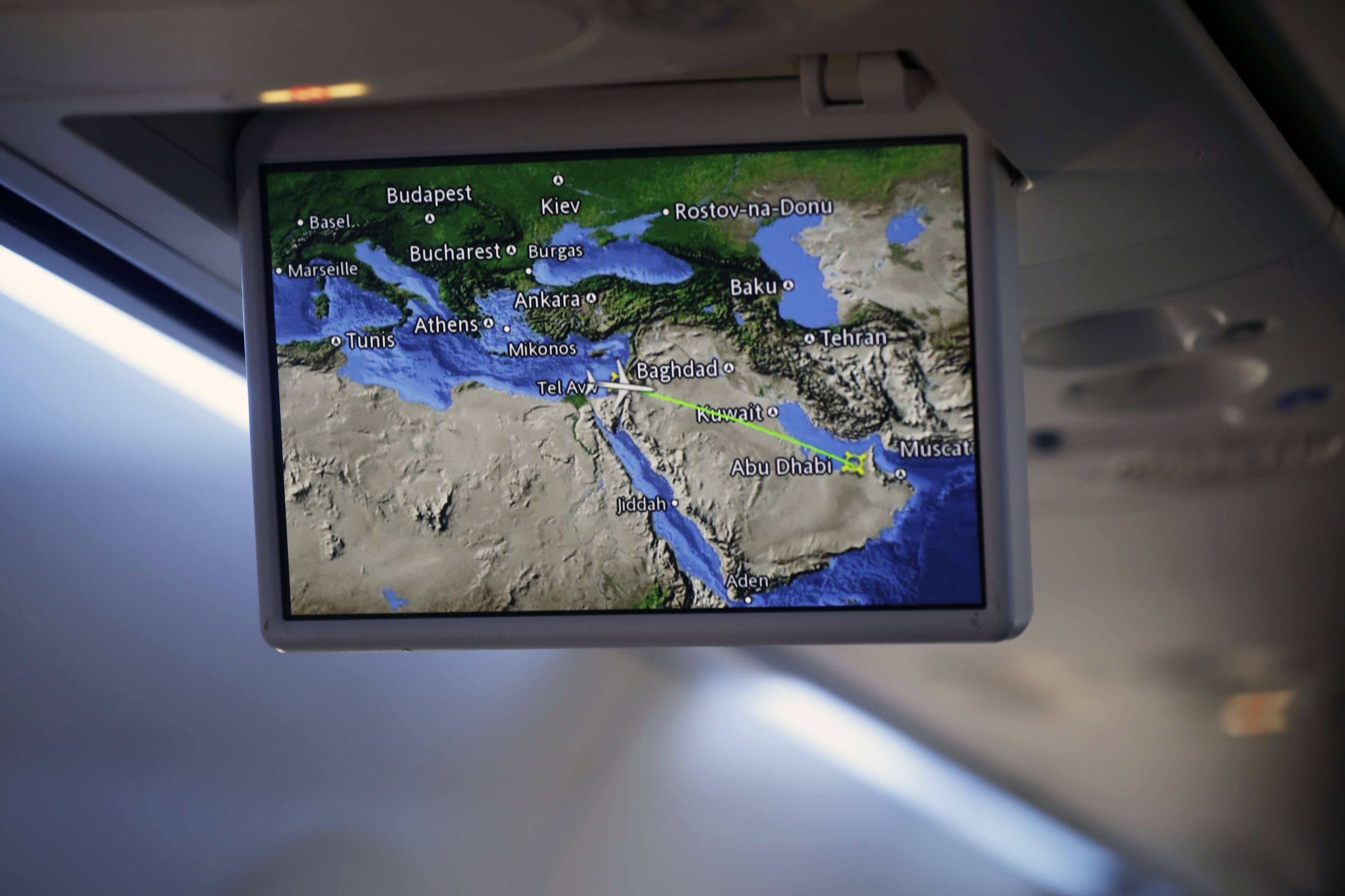 """FILE- In this Monday, Aug. 31, 2020 file photo, an overhead screen displays a map showing the flight route of an El Al plane from Israel en route to Abu Dhabi, United Arab Emirates. The Saudi Press Agency announced Wednesday, Sept. 2, 2020, that it will allow flights """"from all countries"""" to cross its skies to reach the United Arab Emirates. The announcement comes just days after Saudi Arabia allowed the first direct Israeli commercial passenger flight to use its airspace to reach the UAE, signaling acquiescence for a breakthrough U.S.-brokered deal by the United Arab Emirates to normalize relations with Israel. (Nir Elias/Pool Photo via AP, File)"""