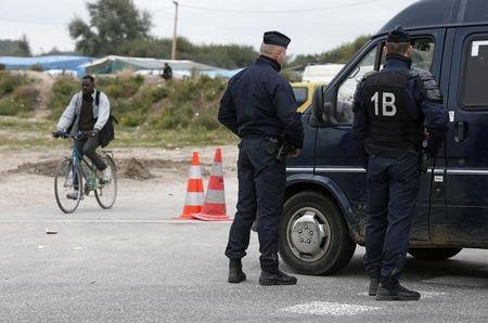 """French Gendarmes stand outside the """"Jungle"""", a migrant camp in Calais, France, October 12, 2016. REUTERS/Pascal Rossignol"""