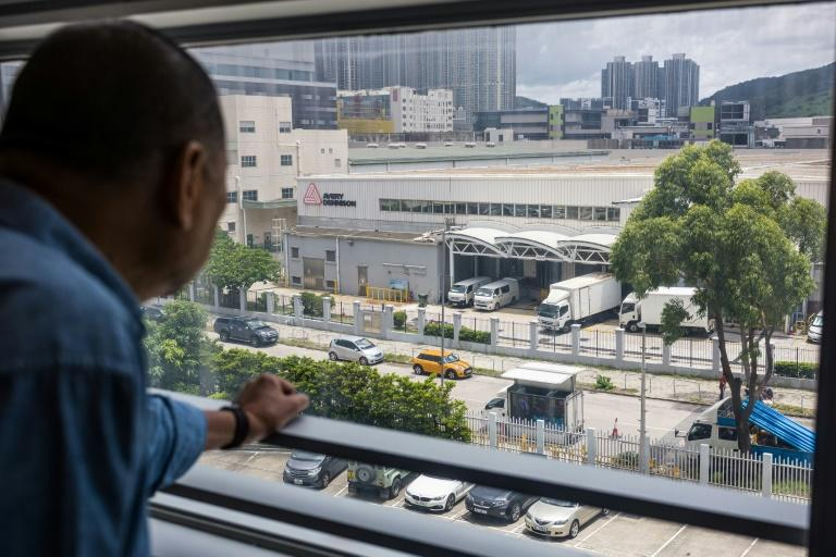 Jimmy Lai looks out of his office window towards a screen broadcasting allegations and conspiracy theories about the tycoon (AFP Photo/Anthony WALLACE)
