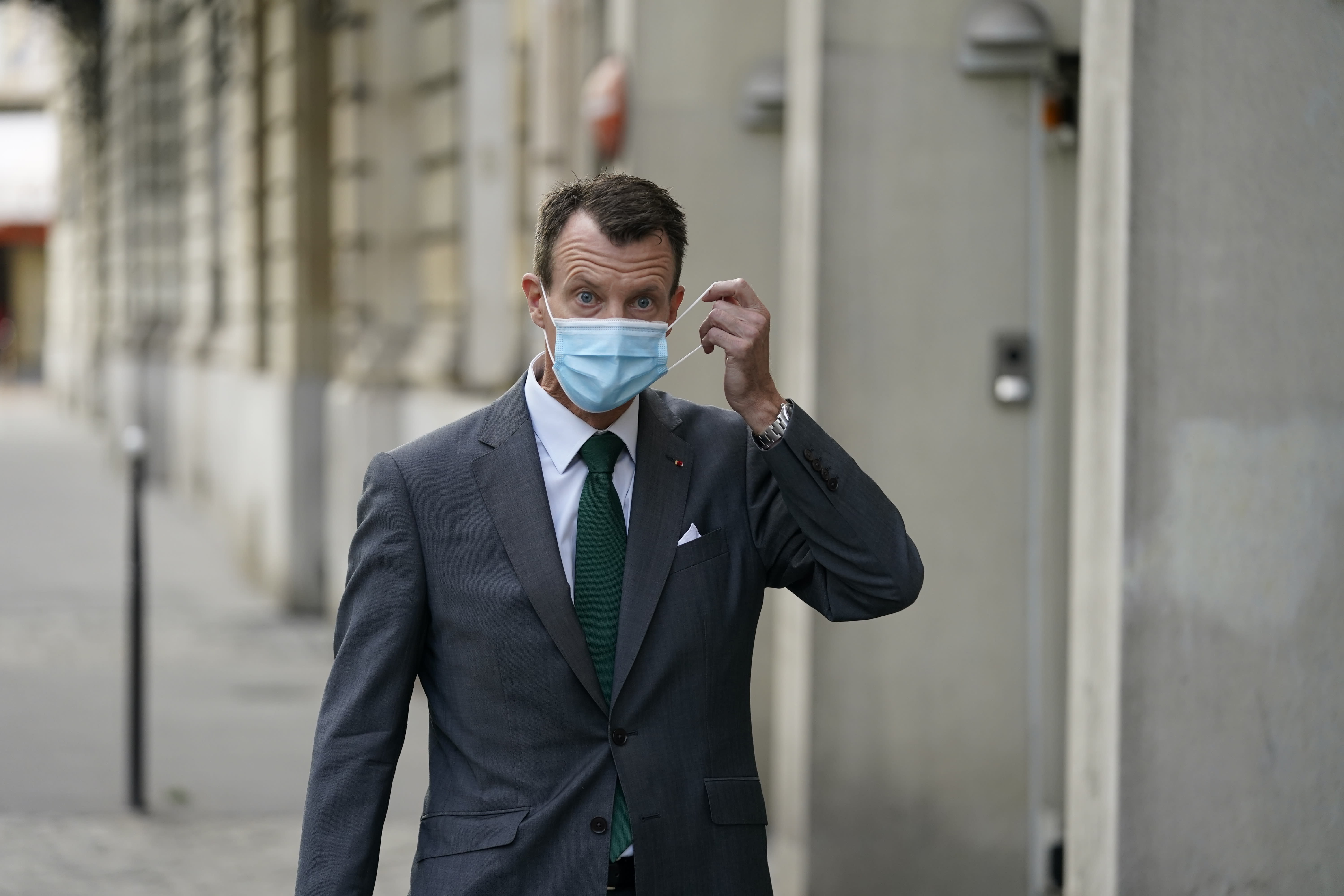 """Denmark's Prince Joachim adjusts his face mask as he walks to work, at the Danish Embassy in Paris, France, Friday, Sept. 18 2020. Prince Joachim, the younger son of Queen Margrethe of Denmark, who underwent an emergency surgery in France in July for a blood clot in his brain, says he is """"eager to get started"""" as he arrived for his first work day at the Danish Embassy in Paris. The 51-year-old prince spoke to reporters outside the Danish mission where he will be defense attache. Joachim was rushed to the Toulouse University Hospital on July 24. (Mads Claus Rasmussen/ Ritzau Scanpix via AP)"""
