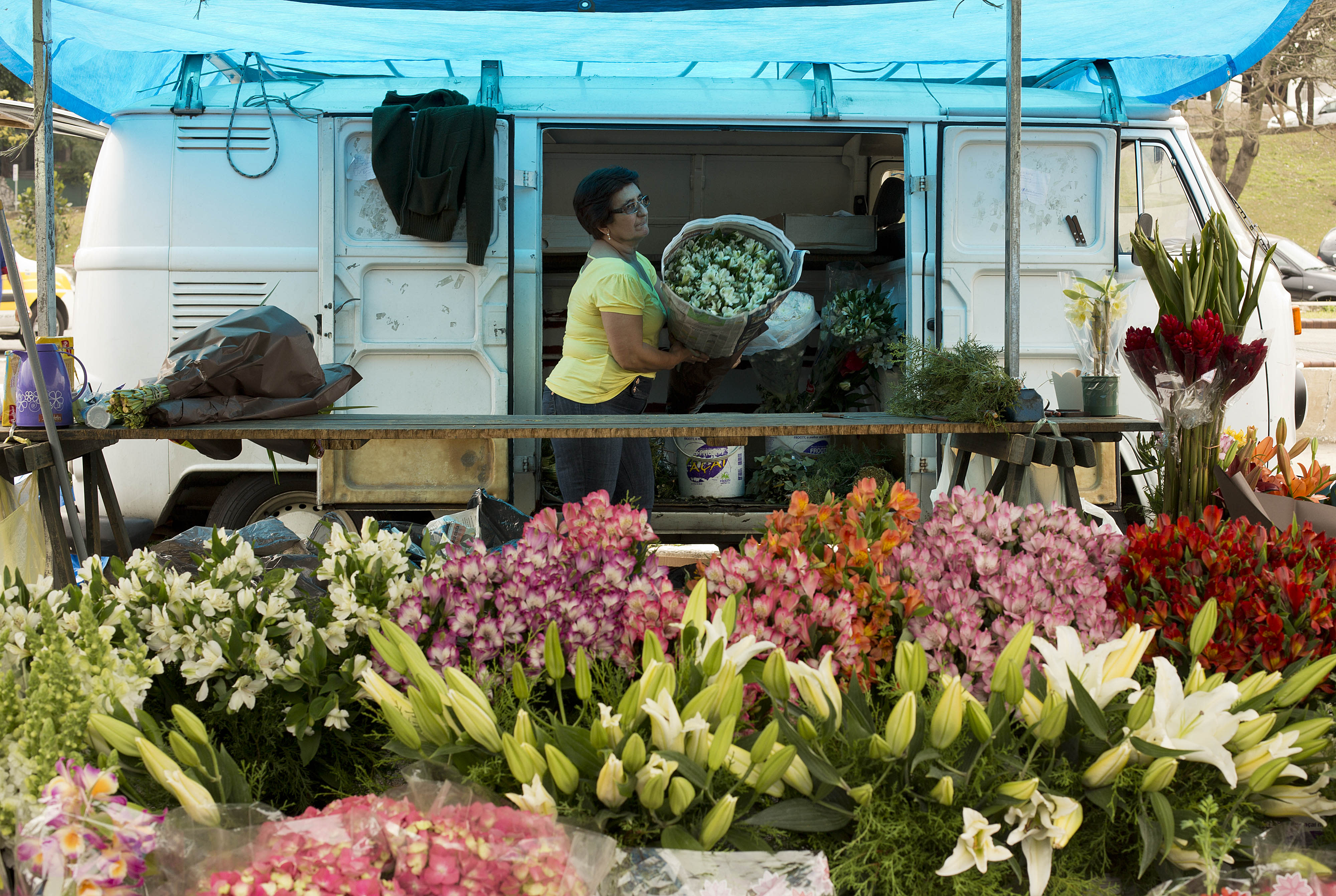 """In this Sept. 3, 2013 photo, a vendor unloads a bouquet of flowers from her Volkswagen van, at a street market in Sao Paulo, Brazil. In Brazil the VW van is known as the """"Kombi,"""" an abbreviation for the German """"Kombinationsfahrzeug"""" that loosely translates as """"cargo-passenger van."""" It's used in Brazil by the postal service to haul mail, by the army to transport soldiers, and by morticians to carry corpses. It serves as a school bus for kids, operates as a group taxi, and delivers construction materials to work sites, but VW says production will end Dec. 31. (AP Photo/Andre Penner)"""