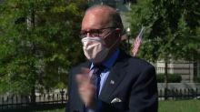 Kudlow puts on a mask at the request of reporters