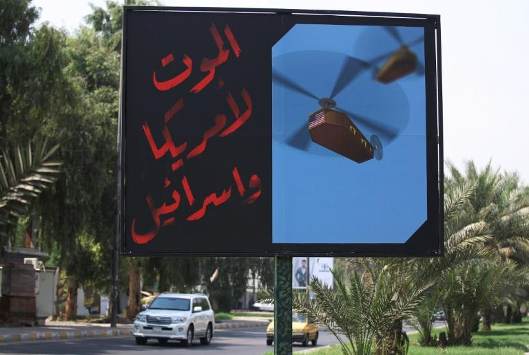"""A billboard installed by a faction of Iraq's Hashed al-Shaabi paramilitary force on a main road in Baghdad reads: """"Death to America and Israel"""", next to a picture of a helicopter carrying a coffin draped with the US flag (AFP Photo/AHMAD AL-RUBAYE)"""
