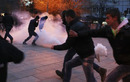 Protesters react to tear gas during a demonstration in the centre of Pristina