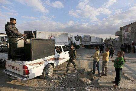 Forces loyal to Syria's president Bashar al-Assad stand by as an aid convoy of the Syrian Arab Red Crescent enters the Wafideen Camp, which is controlled by Syrian government forces, to deliver aid into the rebel-held besieged Douma neighborhood of Damascus, Syria March 4, 2016. REUTERS/Omar Sanadiki