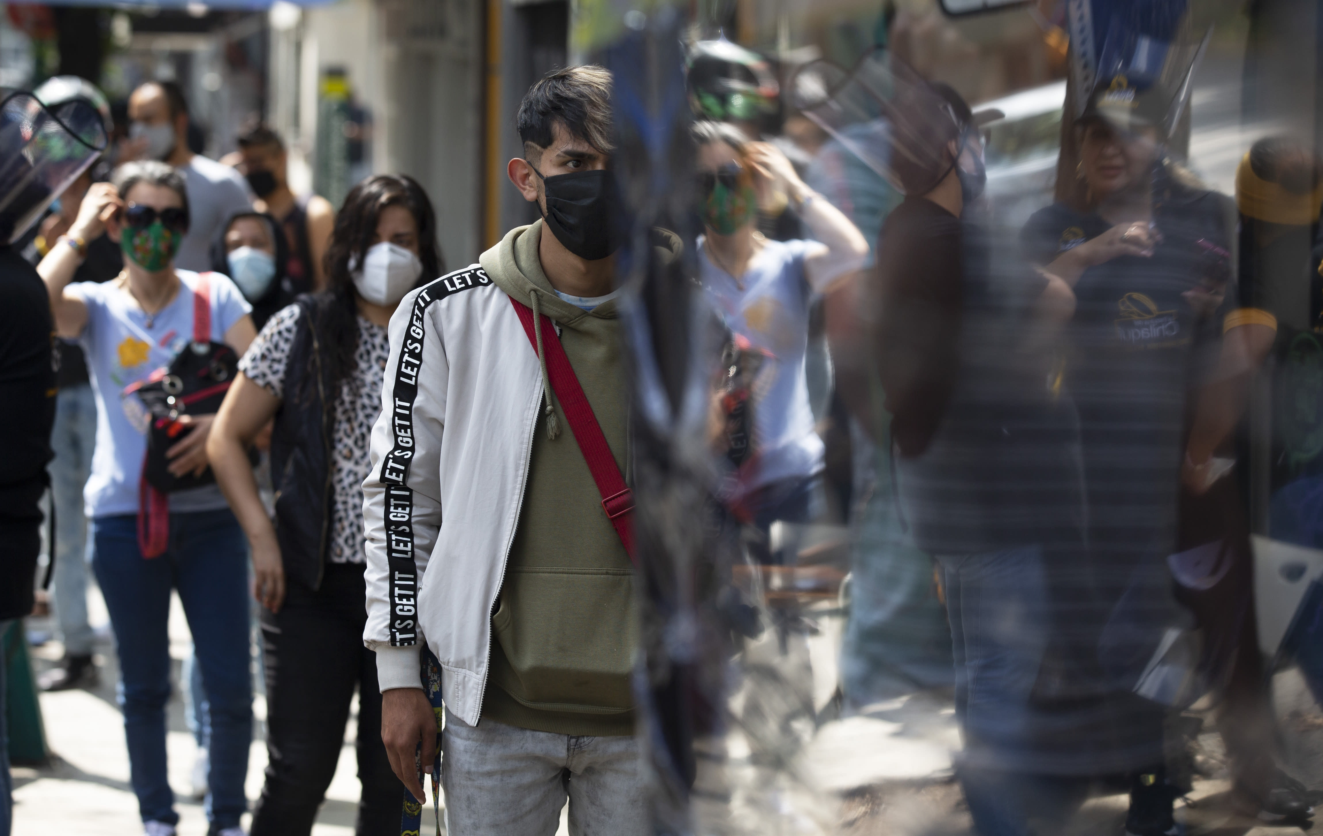 """Customers, wearing protective face masks amid the new coronavirus pandemic, stand in line at a stall selling """"torta de chilaquiles"""", in Mexico City, Saturday, Aug. 1, 2020. Mexico has imposed a very lax and partial lockdown of economic activity that has not stopped high levels of contagion, but has strangled the economy. (AP Photo/Marco Ugarte)"""