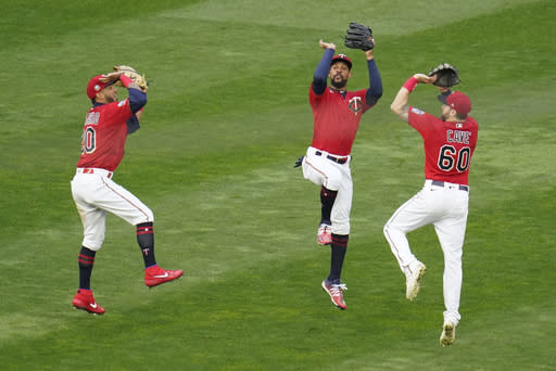 Minnesota Twins outfielders, from left to right, Eddie Rosario, Byron Buxton and Jake Cave show their basketball jump shot skills after they defeated the Detroit Tigers in a baseball game Monday, Sept. 7, 2020, in Minneapolis. (AP Photo/Jim Mone)