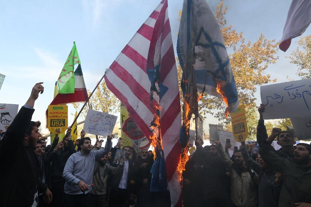 Iranian protesters burn US and Israeli makeshift flags in Tehran on November 4, 2018, on the eve of renewed sanctions by Washington