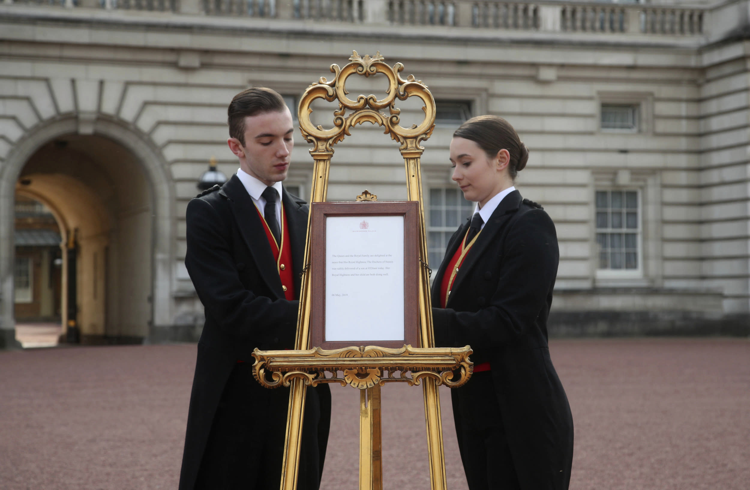 Footmen Stephen Kelly and Sarah Thompson bring out the easel in the forecourt of Buckingham Palace to formally announce the birth of a baby boy to  Britain's Prince Harry and Meghan, the Duchess of Sussex, in London, Monday, May 6, 2019. (Yui Mok/Pool Photo via AP)
