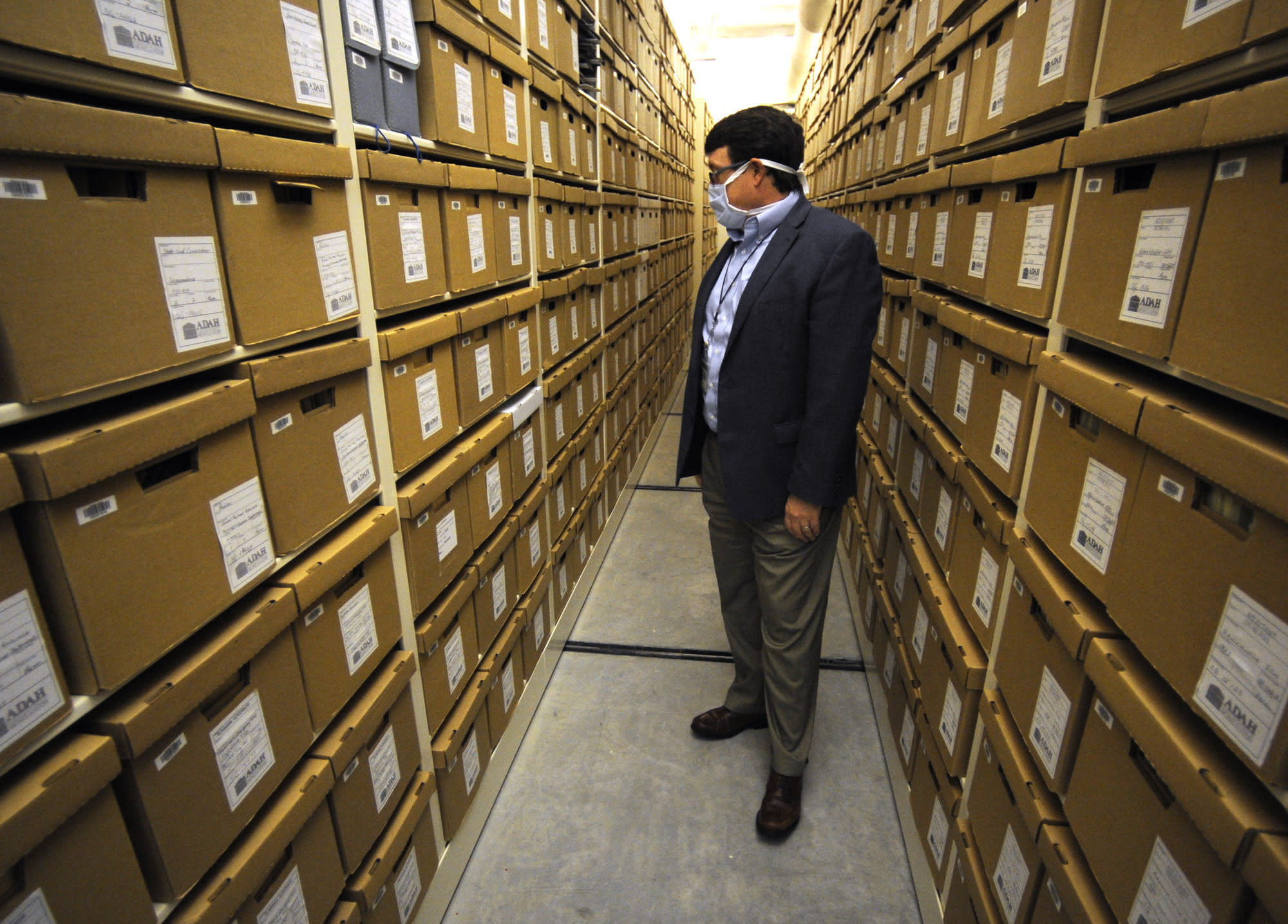 """Steve Murray, director of the Alabama Department of Archives and History, looks through boxes containing archival materials in Montgomery, Ala., on Thursday, Aug. 13, 2020. Murray and other current leaders of the agency are confronting the early legacy of the department, which once embraced the """"lost cause"""" version of Civil War history that diminished the role of slavery and portrayed the Southern cause as noble. (AP Photo/Jay Reeves)"""